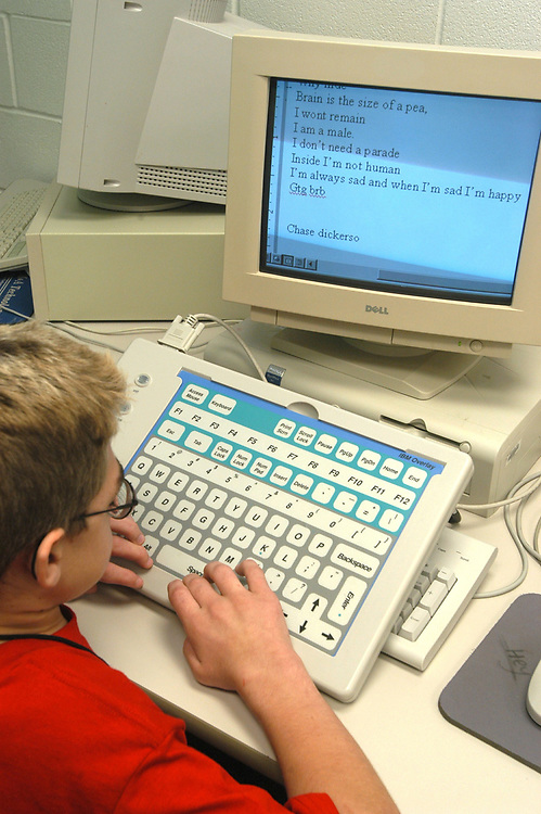 Mabank, Texas September 10, 2003: MODEL RELEASE SP73 (boy in red) . 12 year old with Hurler's Syndrome in writing class with Intellikeys augmentative keyboard and CCTV magnifier that helps him read books. Mabank Independent School District. ©Bob Daemmrich