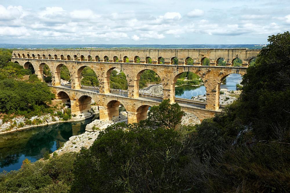 View of Pont du Gard (Roman Aqueduct), the reflective Gardon River, and Garrigue Natural Area, Vers-Pont-du-Gard, France.