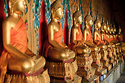 "09 MARCH 2009 -- BANGKOK, THAILAND: Buddhas at Wat Arun. Wat Arun is a Buddhist temple (wat) in the Bangkok Yai district of Bangkok, Thailand, on the west bank of the Chao Phraya River. The full name of the temple is Wat Arunratchawararam Ratchaworamahavihara. The outstanding feature of Wat Arun is its central prang (Khmer-style tower). It may be named ""Temple of the Dawn"" because the first light of morning reflects off the surface of the temple with a pearly iridescence. Steep steps lead to the two terraces. The height is reported by different sources as between 66,80 m and 86 m. The corners are surrounded by 4 smaller satellite prangs. The prangs are decorated by seashells and bits of porcelain which had previously been used as ballast by boats coming to Bangkok from China. The central prang is topped with a seven-pronged trident, referred to by many sources as the ""trident of Shiva"". Around the base of the prangs are various figures of ancient Chinese soldiers and animals. Over the second terrace are four statues of the Hindu god Indra riding on Erawan. The temple was built in the days of Thailand's ancient capital of Ayutthaya and originally known as Wat Makok (The Olive Temple). In the ensuing era when Thonburi was capital, King Taksin changed the name to Wat Chaeng. The later King Rama II. changed the name to Wat Arunratchatharam. He restored the temple and enlarged the central prang. The work was finished by King Rama III. King Rama IV gave the temple the present name Wat Arunratchawararam. As a sign of changing times, Wat Arun officially ordained its first westerner, an American, in 2005. The central prang symbolizes Mount Meru of the Indian cosmology. The satellite prangs are devoted to the wind god Phra Phai..Photo by Jack Kurtz"