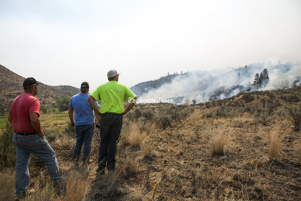 Residents of Okanogan keep an eye on wildfire creeping towards a friend's property off Vic Smith Road west of Conconully Road in central Washington Friday August 21, 2015.<br /> <br /> Bettina Hansen / The Seattle Times