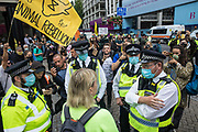 Metropolitan Police officers prepare to arrest an animal rights activist from Animal Rebellion who had made a speech close to a truck being used by fellow activists to blockade the Department of Health and Social Care on 3 September 2020 in London, United Kingdom. Animal Rebellion activists are protesting in solidarity with victims of the global food system and to demand that the UK transitions to a sustainable plant-based food system.