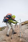 Liana Welty carefully descends fixed chains installed over slick bedrock on the trail from Sorvagen to Munkebu Hut on Moskenesoya, Lofoten Islands, Norway.