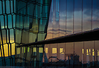 Sunset reflecting color in the glass windows of the Harpe Building in downtown Reykjavik, Iceland
