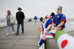 © Licensed to London News Pictures. <br /> 24/05/2014. <br /> <br /> Saltburn, United Kingdom.<br /> <br /> A couple walk along Saltburn pier and look at the knitting that has appeared there overnight. <br /> <br /> The Saltburn Yarn Stormers, a secret group of knitters based around the town have struck once again and produced their latest work in the build up to the World Cup by creating knitted figures representing the countries taking part in the World Cup in Brazil later in the year.<br /> <br /> The identities of the group members which remains a secret launched their most recent creation in the early hours to avoid possible detection and secretly gathered to attach the figures to the railings on the Victorian pier in the town before melting away back in to the shadows.<br /> <br /> Photo credit : Ian Forsyth/LNP