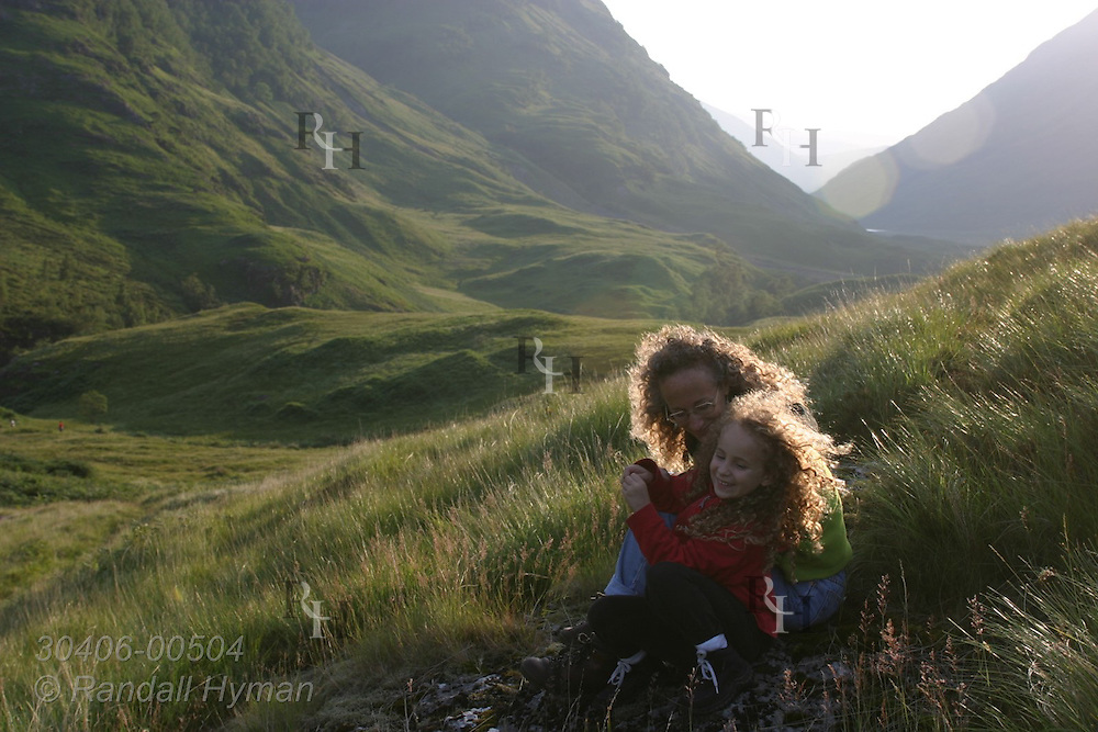 Mother and daughter cuddle in grassy field of upper Glen Coe on a July afternoon; Glencoe Scotland.