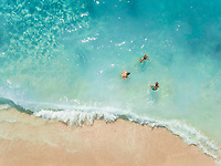 NIKITAS, GREECE - 13 JULY 2018: Aerial view of kids playing in the waves on sandy beach in turquoise sea.