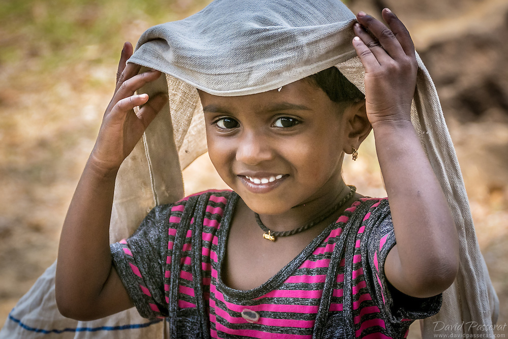 This young girl walking by the Kuruva river in Kerala waved me hello and was eager to be taken in picture. <br /> She lift her veil to invite me to capture her beautiful smile. <br /> I was enchanted and grateful for this great moment.
