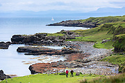 Tourists walking along shoreline at Brothers' Point - Rubha Nam Brathairean - pebbly beach on Isle of Skye, the Western Isles of Scotland, UK