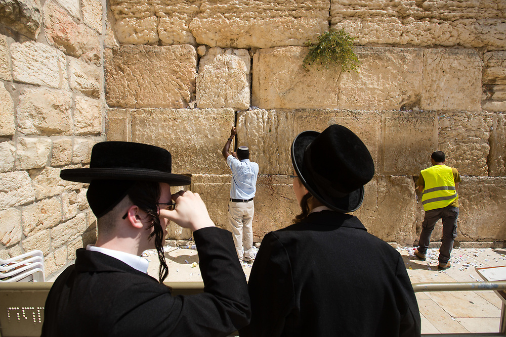 Ultra-Orthodox Jews observe as workers remove notes containing prayers and messages which were left by visitors, from the cracks between the stones of the Western Wall, Judaism's holiest prayer site, in the Old City of Jerusalem, Israel, on September 17, 2017. The clean-up which takes place ahead of the upcoming Jewish New Year Holiday, clears the wall's crevices and frees up space for more notes that people of all faiths slip between its stones, believing that requests deposited at the site are more likely to be heard by God.