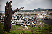 Ruined cars are gathered at temporary site and loading shovels works to rebuild the roads in Minamisanriku town.