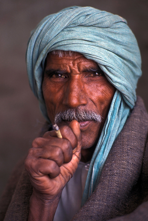 Portrait of a camel herder smoking a bidi cigarette,, Bikaner region, Rajasthan