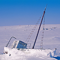 A fishing boat lies frozen into the Arctic Ocean
