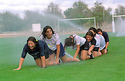 Girls from Tecnico and Vilamoura teams having fun on grass springlers on the rugby field
