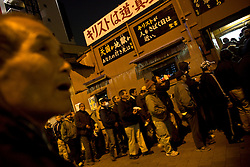 People wait in line to receive charity meal at church in Kamagasaki, Japan.