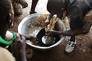 Muddy water containing gold dust. The gold is extracted using mercury which bind with gold. The small ball is 4.5 gr of gold worth $126.00, covered with mercury. The mines in the small community near Bolgatange in Northern Ghana are dug with shovels and spades and held up by timber, all very precarious. The mine shafts go deep into the ground and run along under the surrounding fields. The small community which has sprung up around the gold finds consists of poor people from all over Northern Ghana,most of them now stuck, not making much money and in dept to their gold dealers.