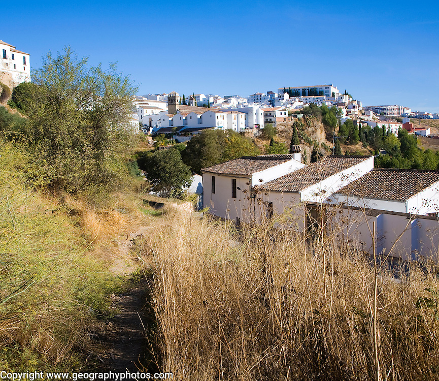 View along path towards white buildings in newer area of Ronda, Spain