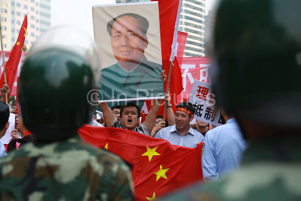 Protestors display banners and pictures of Chairman Mao while chanting slogans during their march towards the Japanese Consulate in Shanghai, China on 16 September 2012. Torrid protests in several Chinese cities broke out against Japan as it tries to nationalize the disputed Senkaku Islands as it is known in Japan or Diaoyu Island as it is known in China for a second day on Sunday, prompting Japanese Prime Minister Yoshihiko Noda to urge Beijing to protect his country's companies and diplomatic buildings from fresh assaults.