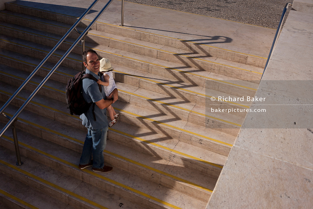 Man carries a child past zigzag shadows of steps at Alameda metro station, Lisbon, Portugal.