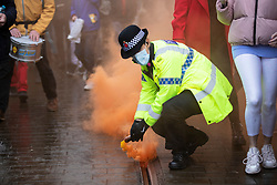 © Licensed to London News Pictures. 12/12/2020. Manchester, UK. A lone police officer picks up a smoke bomb as crowd marches through Manchester with with signs for North Unites protest in Piccadilly Gardens, Manchester. Piers Corbyn is expected to make a speech later. Photo credit: Kerry Elsworth/LNP