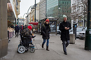 Two Czechs ignore a disabled street beggar in a wheelchair on Vodickova Street, on 19th March, 2018, in central Prague, the Czech Republic.