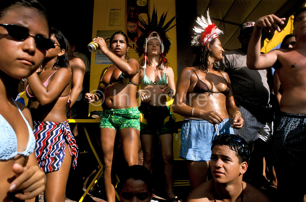 """Men and women drinking and dancing during the celebrations of the  """"Boi Bumba"""" Amazon Carnival, Parintins, Brazil. The carnival serves to celebrate and re-enact Indian traditions and perpetuate myths and legends. It has evolved over time and involves the battle between to opposing bulls, known as Garantido and Caprichoso."""
