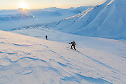 Mylène Jacquemart (front) and Michelle Blade climb a hillside at sunset in Koslådalen, Svalbard.