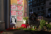 """OAKLAND, CA - JUNE 03: A demonstrator adds flora to a memorial for George Floyd, who died on May 25 whilst in police custody in Minneapolis and other African-Americans killed during police actions, in downtown Oakland, California during a """"Sit Out the Curfew"""" protest on June 3, 2020. - US protesters welcomed new charges against Minneapolis officers in the killing of African-American man George Floyd -- but thousands still marched in cities across the country for a ninth straight night, chanting against racism and police brutality. (Photo by Philip Pacheco/Agence-France Presse/AFP)"""