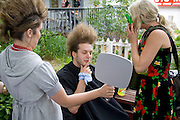 Patron inspecting his new buzz hair style and being photographed in outdoor beauty shop. Grand Old Day St Paul Minnesota USA