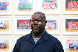 © Licensed to London News Pictures. 11/11/2019. London, UK. Turner Prize-winning artist and Oscar-winning filmmaker Steve McQueen poses for photograph at the preview of his Year 3 exhibition at Tate Britain. An installation of over 3,000 class photographs lining the walls of Tate Britain's Duveen Galleries, depicting more than 70,000 Year 3 pupils from London's primary schools.The exhibition opens on 12 November until 3 May 2020. Photo credit: Dinendra Haria/LNP