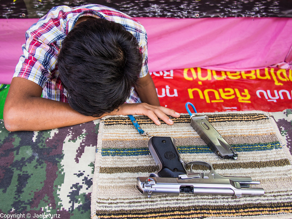 06 FEBRUARY 2014 - HAT YAI, SONGKHLA, THAILAND: A fair carney sleeps next to the shooting game he was working during the Chinese New Year Festival in Hat Yai. Hat Yai was originally settled by Chinese immigrants and still has a large ethnic Chinese population. Chinese holidays, especially Lunar New Year (Tet) and the Vegetarian Festival are important citywide holidays.     PHOTO BY JACK KURTZ