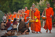 Luang Prabang, Laos. Every morning at dawn, Buddhist monks walk down the streets collecting food alms from devout, kneeling Buddhists, and some tourists. They then return to their temples (also known as wats) and eat together. This procession is called Tak Bat, (Making Merit).