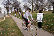 """20 NOVEMBER 2020 - DES MOINES, IOWA: A bicyclist rides past a protest in front of the Iowa Governor's Mansion. About 20 people participated in a protest in front of the Iowa Governor's Mansion Friday. They called on Governor Kim Reynolds to immediately issue a comprehensive mask mandate across Iowa. Reynolds, a Republican, has ordered a partial mask mandate that excuses some congregate settings, like classrooms. Iowa has one of the highest per capita COVID-19 infection rates in the country and is dealing with wide """"community spread"""" of the Coronavirus (SARS-CoV-2) throughout the state.      PHOTO BY JACK KURTZ"""