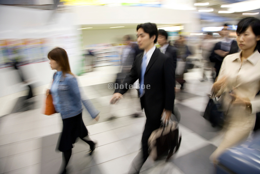 businesspeople at a train station hurrying during rush hour Tokyo Japan