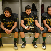 (left-right) Skyhawks cornerback Jarvis Enrico, 16, offensive lineman Miguel Bryant, 17, and wide receiver Deontay Begay, 16, prepare in the locker room Friday night during the delay, in Newcomb.