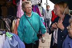 Women at a market stall in the rain,