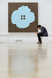 June 8, 2017 - London, UK - London, UK. A visitor sits in front of ''Aqua Button Flower June 30 2015'' by Donald Sultan.  Preview of the Summer Exhibition 2017 at the Royal Academy of Arts in Piccadilly.  Co-ordinated by Royal Academician Eileen Cooper, the 249th Summer Exhibition is the world's largest open submission exhibition with around 1,100 works on display by high profile and up and coming artists. (Credit Image: © Stephen Chung/London News Pictures via ZUMA Wire)