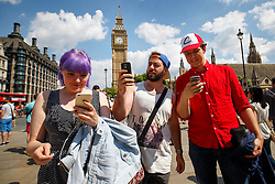 © Licensed to London News Pictures. 23/07/2016. London, UK. Gamers play mobile game Pokémon Go gather in Parliament Square, London to try and capture rare virtual Pokemon characters on Saturday, 23 July 2016. Gamers use their mobile devices to find and capture characters at various real-life locations. Photo credit: Tolga Akmen/LNP