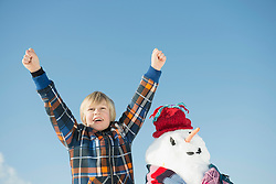 Boy standing with snowman, smiling, Bavaria, Germany