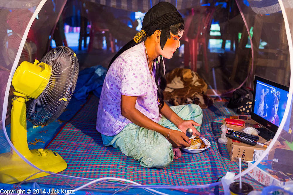 """19 AUGUST 2014 - BANGKOK, THAILAND:  A performer with the Lehigh Leng Kaitoung Opera troupe eats dinner in her mosquito net tent while she watches a Chinese opera on her computer before a performance at the Chaomae Thapthim Shrine, a small Chinese shrine in a working class neighborhood of Bangkok. The performance was for Ghost Month. Chinese opera was once very popular in Thailand, where it is called """"Ngiew."""" It is usually performed in the Teochew language. Millions of Chinese emigrated to Thailand (then Siam) in the 18th and 19th centuries and brought their culture with them. Recently the popularity of ngiew has faded as people turn to performances of opera on DVD or movies. There are still as many 30 Chinese opera troupes left in Bangkok and its environs. They are especially busy during Chinese New Year and Chinese holiday when they travel from Chinese temple to Chinese temple performing on stages they put up in streets near the temple, sometimes sleeping on hammocks they sling under their stage. Most of the Chinese operas from Bangkok travel to Malaysia for Ghost Month, leaving just a few to perform in Bangkok.        PHOTO BY JACK KURTZ"""