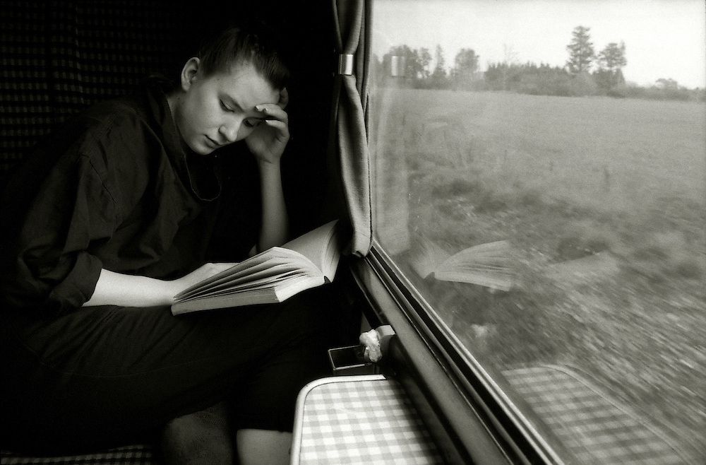 A young woman reading a novel on a train journey.
