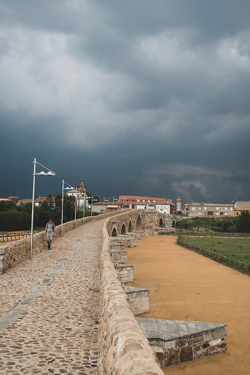 A pilgrim crosses the 13th-century bridge, sometimes called the Puente del Passo Honroso, into Hospital de Órbigo, Spain. From here, 250 kilometers remain on the Camino before reaching Santiago de Compostela. (June 28, 2018)<br /> <br /> DAY 32: STAYED IN HOSPITAL DE ORBIGO