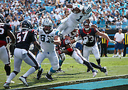Carolina Panthers quarterback Cam Newton (1) gets hit by Houston Texans free safety Rahim Moore (26) as he leaps head over heels into the end zone on a 2 yard touchdown run good for a 17-10 third quarter lead during the 2015 NFL week 2 regular season football game against the Houston Texans on Sunday, Sept. 20, 2015 in Charlotte, N.C. The Panthers won the game 24-17. (©Paul Anthony Spinelli)
