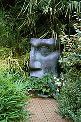 Large metal statue and decking surrounded by foliage planting in a small town garden