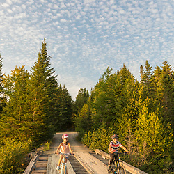 Kids ride bikes on Bridge over the Red River at Pushineer Pond in Aroostook County, Maine. Deboullie Public Reserve Land.