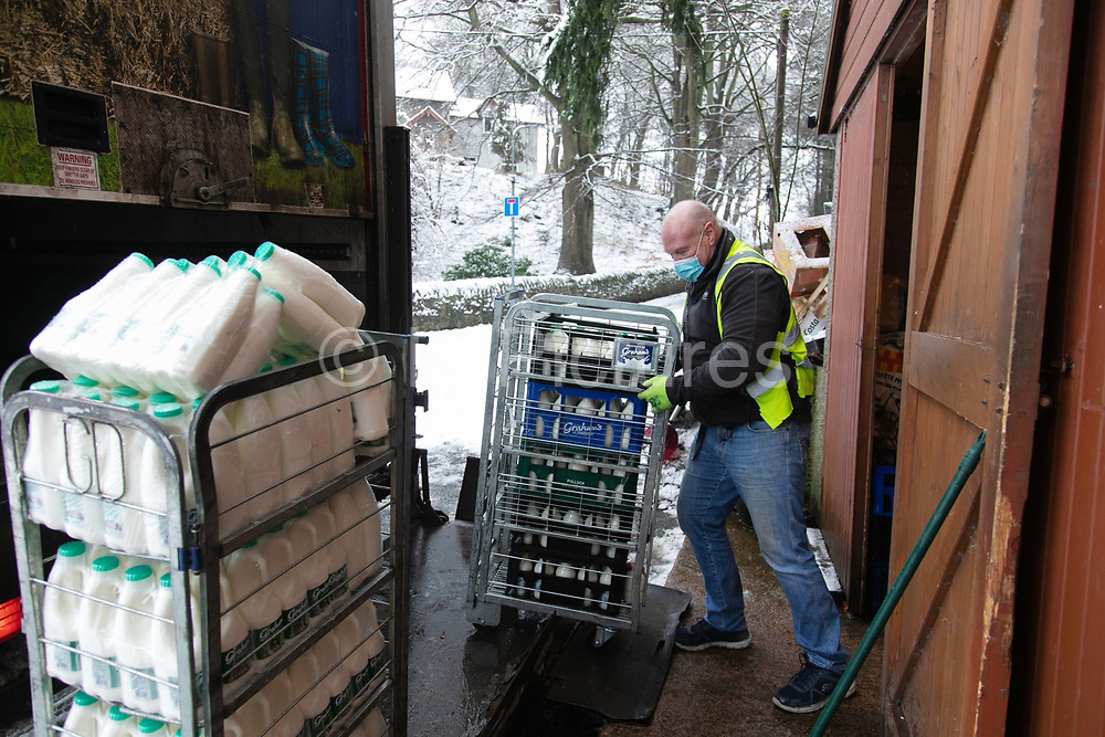 Milkman Gordon Anderson receives fresh diary products on 14th of January 2021 in Stow, Scottish Borders, United Kingdom. Gordon Anderson runs a fresh milk and vegetables delivery service with his wife and they deliver to local houses and farms in and around the village of Stow. They keep their fresh products in a small shed in the centre of town and get their deliveries from the diary company Graham's.