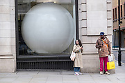 Large white ball in the window of a building in Mayfair on 12th April 2021 in London, United Kingdom. This huge scale sphere interacts with passing people.