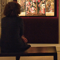 """VENICE, ITALY - JANUARY 10:  A member of staff admires """"Triptych of the Martyrdom of St Liberatal"""" panels by Hieronymus Bosch on display at Palazzo Grimani on January 10, 2011 in Venice, Italy. The  exhibition will be open until 20th March 2011."""