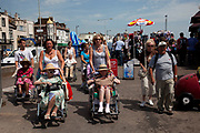 Elderly ladies in wheelchairs are pushed along the front by their carers at Southend-on-sea, Essex. Thier are an extraordinary number of disabled people in Southend. The town could be described as run down as while there are some signs of affluence, these are few and far between. The predominant atmosphere is quite rough feeling and quite poor. Southend is a seaside resort that is very popular with people from the East side of London due to it's close proximity, just an hour away by train along the Thames Gateway. With the decline of seaside resorts, from the 1960s much of the centre was developed for commerce and many of the original features were destroyed through redevelopment or neglect.