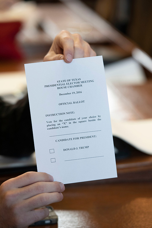 Austin Texas December 19, 2016:  Elector casts a ballot as Texas electors to the U.S. Electoral College meet at the Texas Capitol to cast votes for President Donald Trump and Vice-President Mike Pence.  Hundreds of protesters chanted outside the Capitol during the vote.