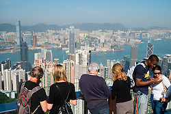 Tourists looking at skyline of Hong Kong from The Peak